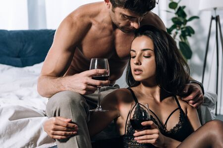sexy man embracing seductive girlfriend while holding glasses of red wine Standard-Bild - 137760588