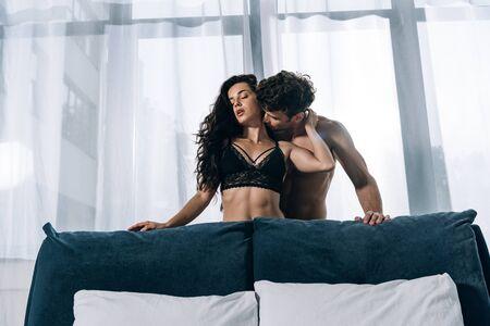 sexy man kissing seductive girlfriend in black lingerie near window in bedroom Standard-Bild - 137760596
