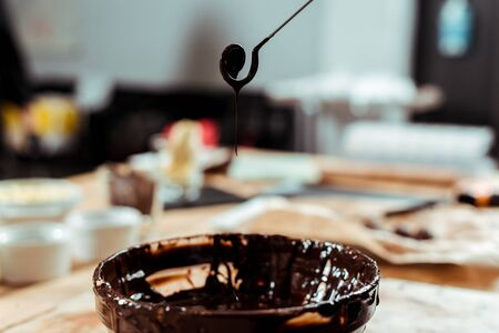 selective focus of swirl beater with drops of melted chocolate near bowl Reklamní fotografie