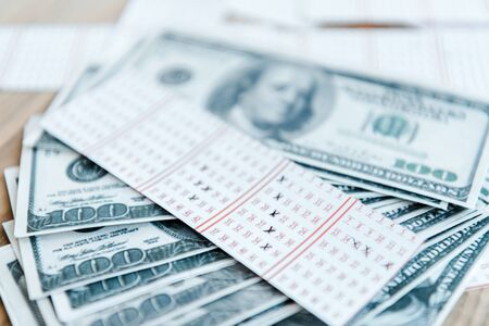 selective focus of marked lottery ticket near dollar banknotes on table