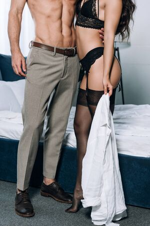 cropped view of sexy shirtless man in trousers embracing girlfriend in black lingerie Stock Photo