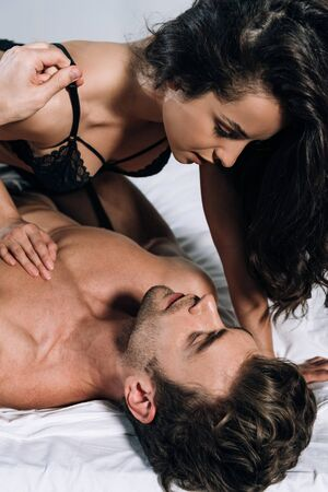 seductive woman looking at sexy man while lying on him in bed Stock Photo