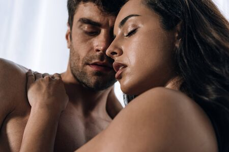 young, passionate couple hugging with closed eyes