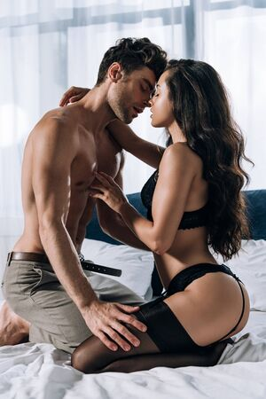 shirtless man in trousers and woman in black lingerie and stockings embracing on bed