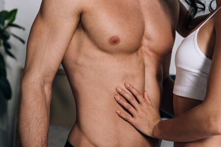 cropped view of girl touching muscular torso of boyfriend
