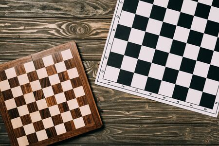 Top view of two chessboards on textured wooden