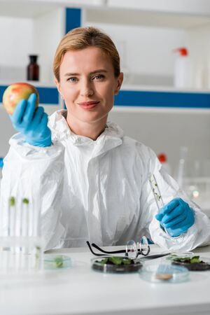 Selective focus of smiling biologist holding whole apple and test tube in lab