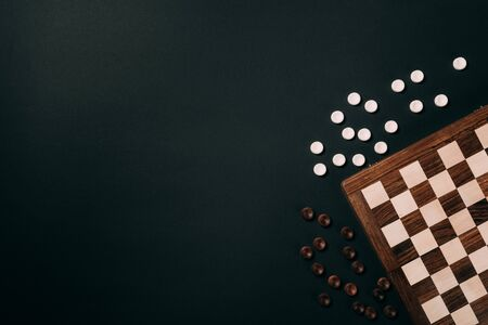 Top view of checkers by checkerboard isolated on black with copy space