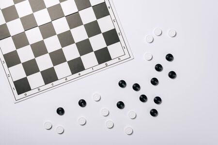 Top view of chessboard and checkers isolated on white