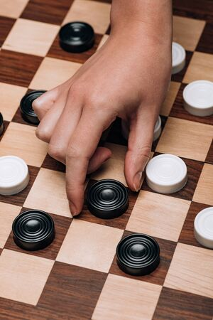 Cropped view of woman holding black checker on wooden checkerboard
