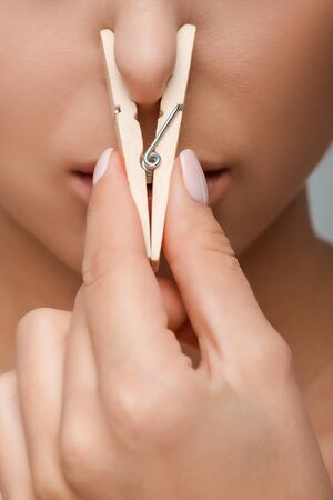 Cropped view of young woman touching wooden pin near nose Imagens