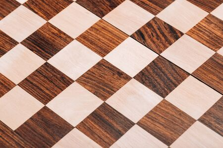 Surface of folding wooden checkerboard with brown and white squares