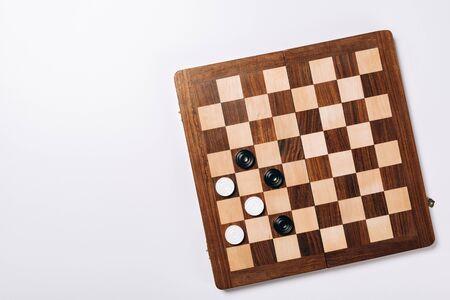 Draufsicht der Dame auf hölzernem Schachbrett auf weißem Hintergrund