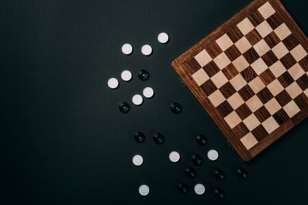 Top view of checkers beside wooden checkerboard isolated on black
