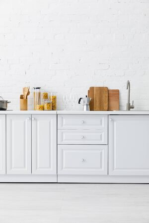 Minimalist modern white kitchen interior with kitchenware near brick wall Stock Photo