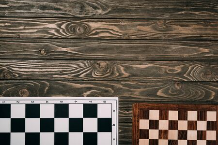 Top view of two checkerboards on wooden background with copy space Banque d'images