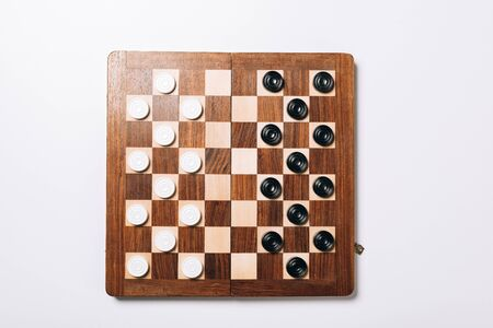 Top view of black and white checkers on wooden checkerboard on white background Standard-Bild