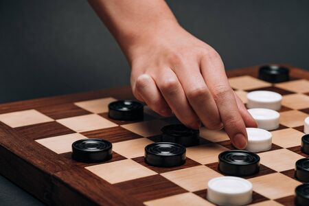 Cropped view of woman playing checkers on grey