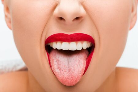 Cropped view of young woman with red lipstick sticking out tongue isolated on white Stock Photo