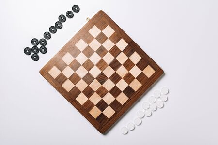 Top view of wooden chessboard and checkers on white background