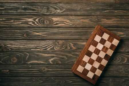 Top view of checkerboard on textured wooden background 版權商用圖片 - 137419479