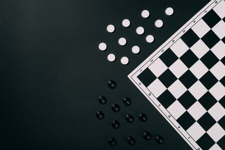 Top view of black and white checkers and checkerboard isolated on black Standard-Bild
