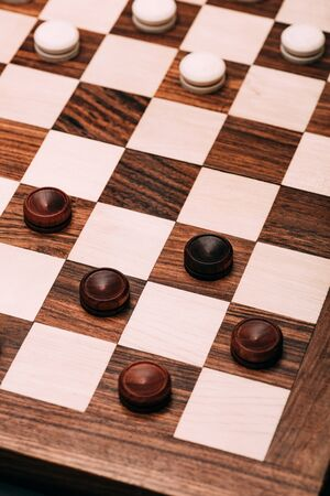 High angle view of checkers on wooden checkerboard