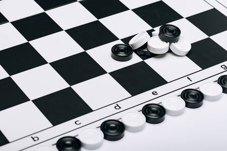 High angle view of checkers on checkerboard isolated on white 版權商用圖片