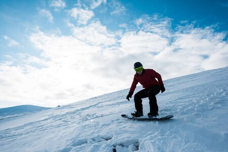 athletic snowboarder riding on slope against blue sky in winter