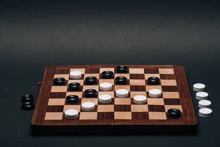 Checkerboard with black and white checkers isolated on black