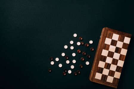 Top view of white and brown checkers with chessboard isolated on black