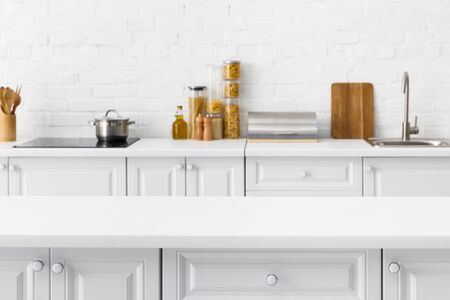 selective focus of empty tabletop and minimalistic modern white kitchen interior with kitchenware and food near brick wall on background