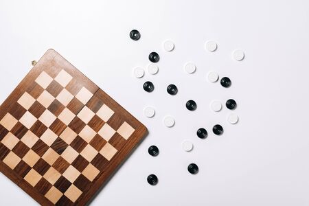 Top view of checkers by wooden checkerboard on white background