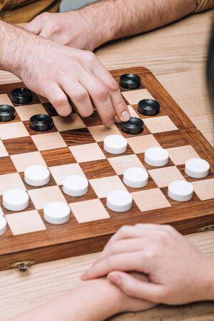 Selektiver Fokus von Mann und Frau, die Dame am Holztisch spielen