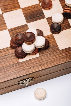 High angle view of wooden checkers on checkerboard isolated on white 版權商用圖片