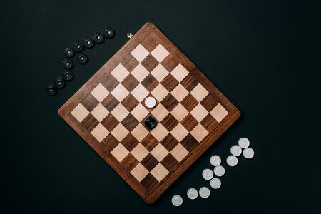 Top view of checkers on wooden chessboard isolated on black
