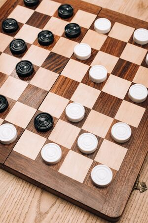High angle view of checkers on checkerboard on wooden table 版權商用圖片