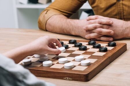 Cropped view of man and woman playing checkers at table Standard-Bild