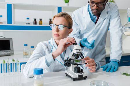 Multiculturele biologen in witte jassen met behulp van microscoop in lab