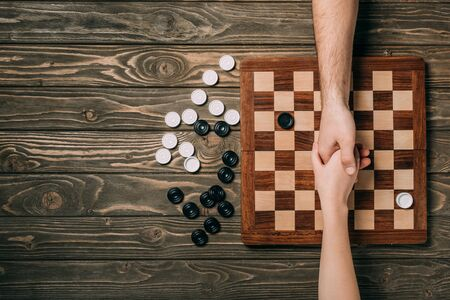 Cropped view of man and woman shaking hands above checkerboard with checkers on wooden background Standard-Bild
