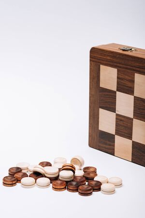 Pile of wooden checkers by checkerboard isolated on white 版權商用圖片 - 137420061