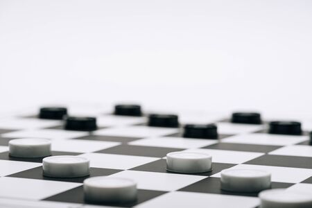 Selective focus of checkers on chessboard isolated on white