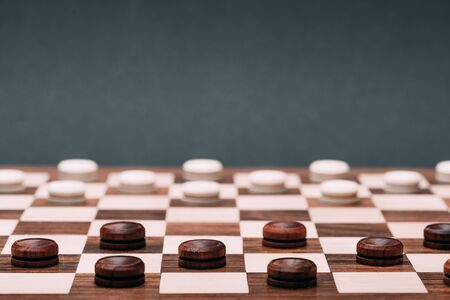 Selective focus of checkers on checkerboard isolated on grey Standard-Bild