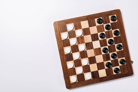 Top view of black and white checkers on wooden chessboard on white background