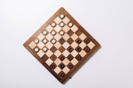 Top view of checkers on wooden chessboard on white background