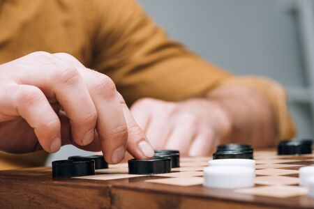 Cropped view of man playing checkers on wooden checkerboard