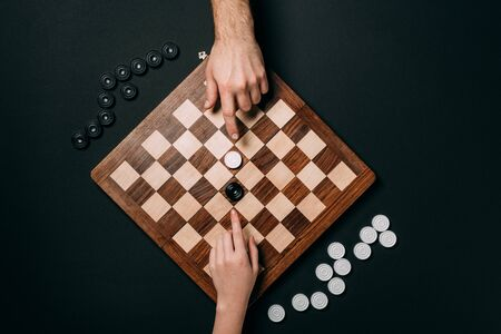 Top view of man and woman playing checkers isolated on black