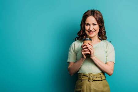 cheerful girl looking at camera while holding coffee to go on blue background