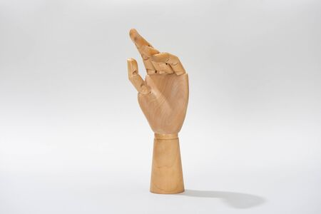 Wooden hand of puppet on grey background