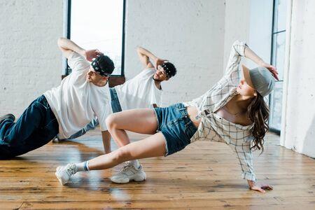 trendy multicultural dancers breakdancing in dance studio
